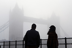 © Licensed to London News Pictures. 12/12/2012. London, UK. Tourists look at Tower Bridge in London during thick freezing fog this morning, 12 December 2012. Photo credit : Vickie Flores/LNP.