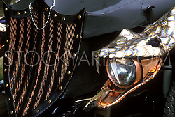 Stock photo of a close up of a headlight held in a sculpted snake's mouth
