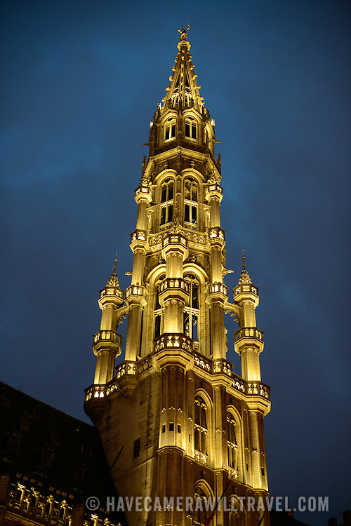 The main tower under lights of the Town Hall (Hotel de Ville) in the Grand Place, Brussels. Originally the city's central market place, the Grand-Place is now a UNESCO World Heritage site. Ornate buildings line the square, including guildhalls, the Brussels Town Hall, and the Breadhouse, and seven cobbelstone streets feed into it.