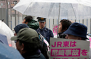 A policeman keeps an eye on marchers at a demo rally organized by Doro Chiba labour union to protest the outsourcing of what they consider essential safety and repair work and fight against rationalization of JR (Japan Railways) business. They also protested for the reinstatement of 1,047 national railway workers who lost their jobs in 1987. Shibuya, Tokyo, Japan Saturday, February 13th 2010