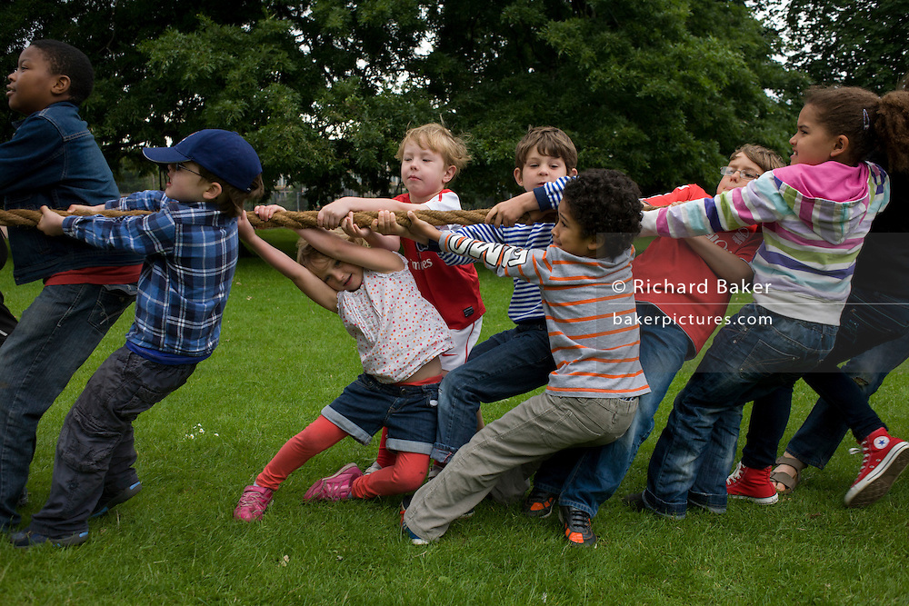 Local children heave-ho on a large rope for the best of three tug o' war games during a community park festival.