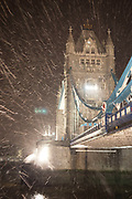Night scene of Tower Bridge in London on a cold winter evening as snow fills the air and is blown by strong wind.