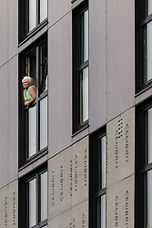 © Licensed to London News Pictures . 12/10/2018. Salford , UK . Thorn Court resident DAWN LEWIS (57) leaning from the window of her flat on the fourth floor with temporary cladding below and unsafe cladding from her level and up . Recently installed cladding at several council-owned tower blocks in Salford has been identified as having similar dangerous properties to that which was installed on the Grenfell Tower in London . Residents have been waiting months for clarification on what action will be taken to make their homes safe . Photo credit : Joel Goodman/LNP