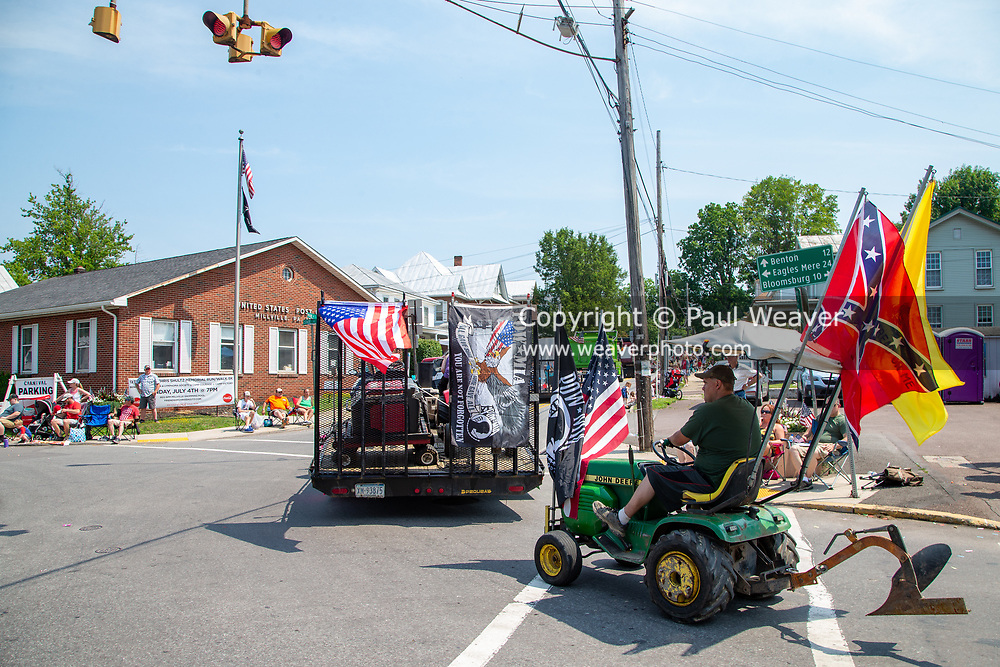 A man is seen driving a lawn tractor with a confederate flag in the Independence Day Parade in Millville, Pennsylvania on July 5, 2021.