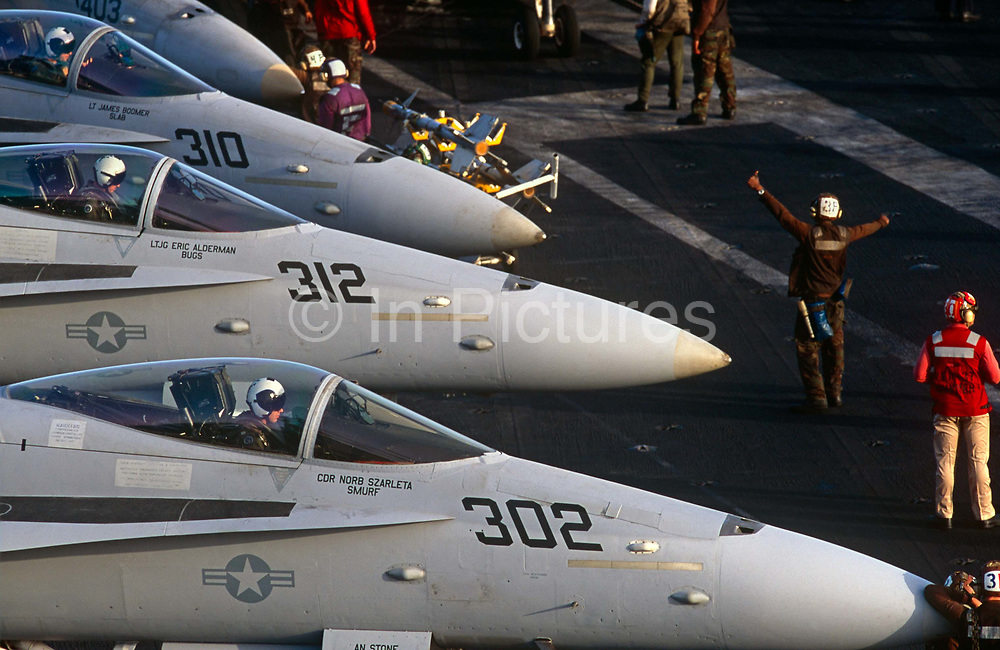 Red shirted ordnance men organise the busy deck of F/A-18C fighter jets on aircraft carrier on deck of USS Harry S Truman. Launched on 7 September 1996 and costing US$4.5 billion, the Truman (CVN-75) is the eighth Nimitz-class supercarrier of the United States Navy, named after the 33rd President of the United States, Harry S. Truman. The Truman is the largest of the US Navy's fleet of new generation carriers, a 97,000 ton floating city with a crew of 5,137, 650 are women.
