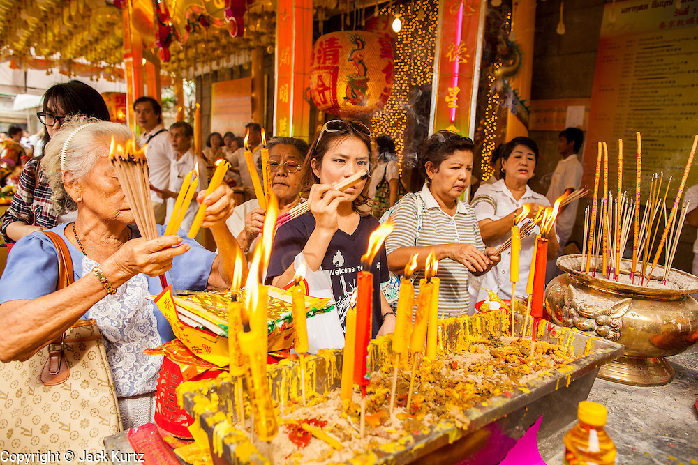 17 OCTOBER 2012 - BANGKOK, THAILAND:  People make offerings in Wat Mangkon Kamalawat, one of the largest Chinese shrines in Thailand, during the Vegetarian Festival in Bangkok. The Vegetarian Festival is celebrated throughout Thailand. It is the Thai version of the The Nine Emperor Gods Festival, a nine-day Taoist celebration celebrated in the 9th lunar month of the Chinese calendar. For nine days, those who are participating in the festival dress all in white and abstain from eating meat, poultry, seafood, and dairy products. Vendors and proprietors of restaurants indicate that vegetarian food is for sale at their establishments by putting a yellow flag out with Thai characters for meatless written on it in red.      PHOTO BY JACK KURTZ