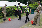 Thames Valley Police officers walk past serving Coldstream Guards soldiers collecting cash for charity <br /> during the annual Royal Ascot horseracing festival in Berkshire, England. Royal Ascot is one of Europe's most famous race meetings, and dates back to 1711. Queen Elizabeth and various members of the British Royal Family attend. Held every June, it's one of the main dates on the English sporting calendar and summer social season. Over 300,000 people make the annual visit to Berkshire during Royal Ascot week, making this Europe's best-attended race meeting with over £3m prize money to be won.