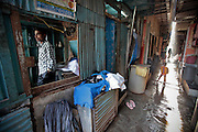 A youngsters who offers ironing services waits for some customers in his stand.  The slum of Cheetah Camp on the outskirts of Mumbai, India is a predominantly muslim community on living on the fringe while the city continues to grow.