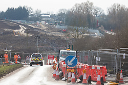 Harefield, UK. 13th February, 2021. A security vehicle approaches a road closure on Harvil Road in the Colne Valley set up in order to facilitate the felling (behind) of some of the few remaining trees in the area for the HS2 high-speed rail link. Four anti-HS2 activists had been evicted from a roadside camp and three from nearby trees by bailiffs acting for HS2 Ltd during the night.