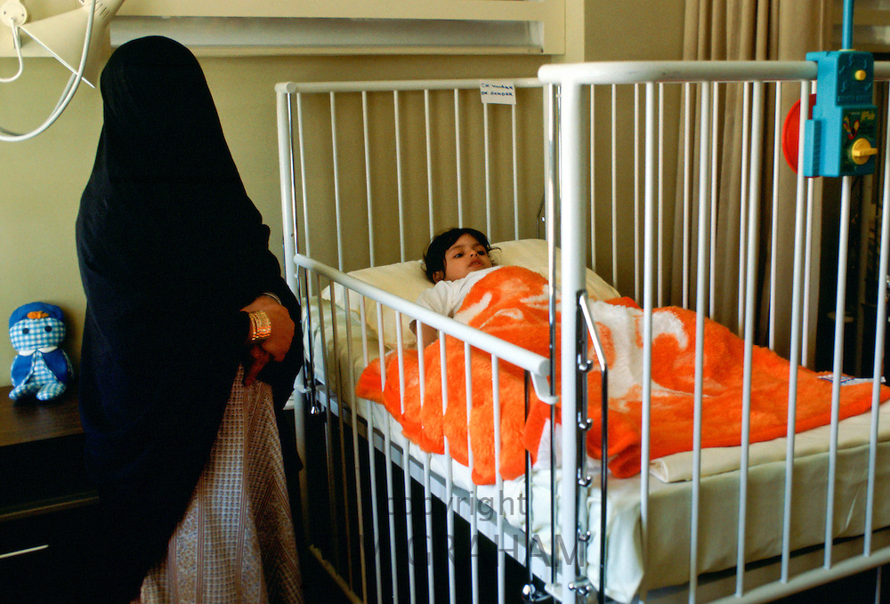 A Saudi mother stays with her child who is in a hospital cot at Moda Hospital in Riyadh, Saudi Arabia