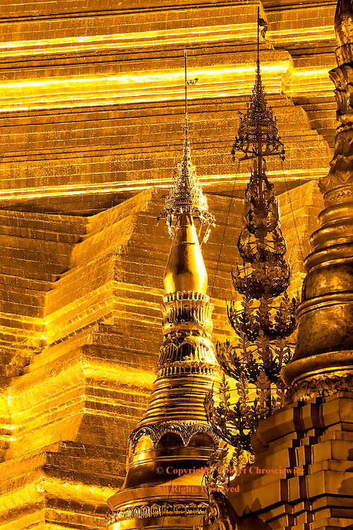 Golden Night Pagoda: A close up view of the base of the main Golden Stupa at night, with three smaller spires in the foreground, at the Shwedagon Pagoda, Yangon Myanmar.
