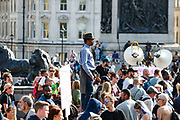 """A man stands on a plinth and watches as Police clashed and arrested protestors during a """"Resist and Act for Freedom"""" protest against a mandatory coronavirus vaccine, wearing masks, social distancing and a second lockdown, nearby Canada House in Trafalgar Square, London on Saturday, Sept. 19, 2020. The event, which began at noon, drew a broad coalition including coronavirus sceptics, 5G conspiracy theorists and so-called """"anti-vaxxers"""". Speakers at the event accused the government of attempting to curtail civil liberties. (VXP Photo/ Vudi Xhymshiti)"""