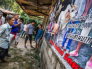 08 FEBRUARY 2014 - PHAWONG, SONGKHLA, THAILAND: People read a poster while they wait to get into a bullfighting ring in a rural part of Songkhla province in southern Thailand. Bullfighting is a popular past time in southern Thailand. Hat Yai is the center of Thailand's bullfighting culture. In Thai bullfights, two bulls are placed in an arena and they fight, usually by head butting each other, until one runs away or time is called. Huge amounts of mony are wagered on Thai bullfights - sometimes as much as 2,000,000 Thai Baht ($65,000 US).   PHOTO BY JACK KURTZ