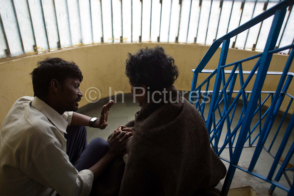 At the Phool Mandi shelter, Khushi Ram, a worker for Aashray Adhikar Abhiyan counsels Kulbahadur a former drug addict from Nepal that has been treated for schizophrenia. Delhi, India