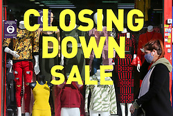 © Licensed to London News Pictures. 19/10/2020. London, UK. A woman wearing a face covering in north London walks past 'CLOSING DOWN SALE' sign a shop window which is closing due to coronavirus crisis. According to the figures, revealed by the Local Data Company and advisory firm PricewaterhouseCoopers (PwC), a total of 11,120 shops on UK high streets closed in the first half of this year due to the coronavirus lockdown.  Photo credit: Dinendra Haria/LNP
