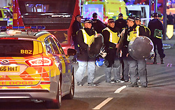 Police officers with riot shields on Borough High Street as police are responding to three incidents in the capital, amid reports that a vehicle collided with pedestrians on London Bridge, Scotland Yard said. Officers are dealing with reports of stabbings in Borough Market, where armed officers attended and shots were fired. They are also at an incident in the Vauxhall area.
