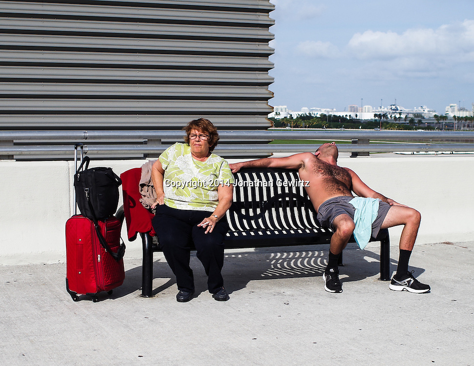 Two people sitting on a sunny bench at a Florida airport.<br /> WATERMARKS WILL NOT APPEAR ON PRINTS OR LICENSED IMAGES.