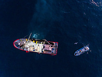 Aerial view of men working at fishing boats during the night, Spain.