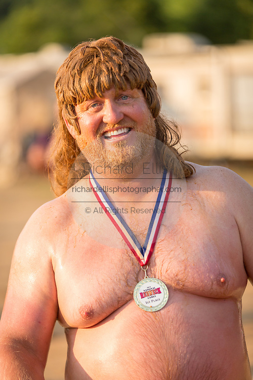 A competitor shows off his medal won in the belly flop contest at the 2015 National Red Neck Championships May 2, 2015 in Augusta, Georgia. Hundreds of people joined in a day of country sport and activities.