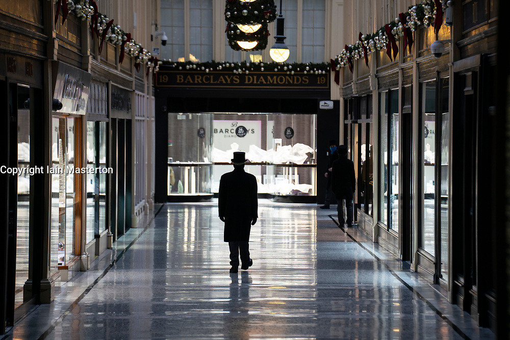 Glasgow, Scotland, UK. 21 November 2020. Views of Saturday afternoon in Glasgow city centre on first day of level 4 lockdown. Non essential shops and businesses have closed. And streets are very quiet. Pictured;  Security guard walks in an empty Argyll Arcade where all shops are closed .Iain Masterton/Alamy Live News