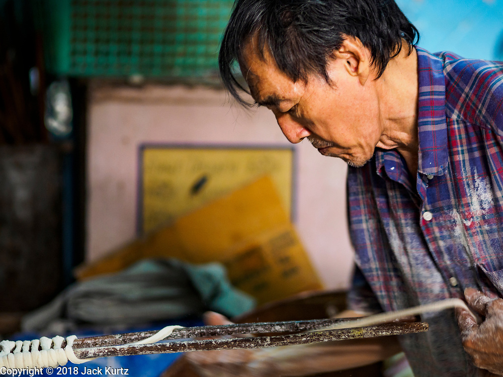 """29 DECEMBER 2018 - BANGKOK, THAILAND: A man makes longevity noodles in his family shophouse. The family has been making traditional """"mee sua"""" noodles, also called """"longevity noodles"""" for three generations in their home in central Bangkok. They use a recipe brought to Thailand from China. Longevity noodles are thought to contribute to a long and healthy life and  are served on special occasions, especially Chinese New Year, which is February 4, 2019. These noodles were being made for Chinese New Year.     PHOTO BY JACK KURTZ"""