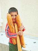 Boy carrying baguettes, El Djem, Tunisia