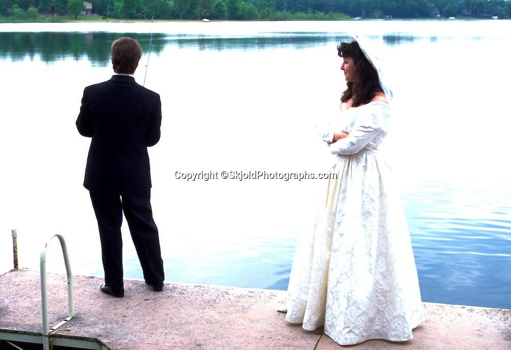 Groom fishing on dock as bride waits impatiently age 27. Roy Lake Nisswa  Minnesota USA