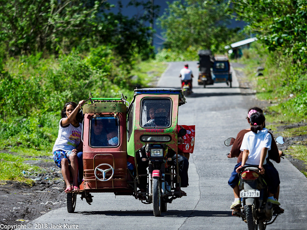 """22 JANUARY 2018 - CAMALIG, ALBAY, PHILIPPINES: People ride a Filipino tricycle taxi while they leave their communities on the slopes of the Mayon volcano. There were a series of eruptions on the Mayon volcano near Legazpi Monday. The eruptions started Sunday night and continued through the day. At about midday the volcano sent a plume of ash and smoke towering over Camalig, the largest municipality near the volcano. The Philippine Institute of Volcanology and Seismology (PHIVOLCS) extended the six kilometer danger zone to eight kilometers and raised the alert level from three to four. This is the first time the alert level has been at four since 2009. A level four alert means a """"Hazardous Eruption is Imminent"""" and there is """"intense unrest"""" in the volcano. The Mayon volcano is the most active volcano in the Philippines. Sunday and Monday's eruptions caused ash falls in several communities but there were no known injuries.    PHOTO BY JACK KURTZ"""