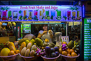 A Cambodian woman slices mango into a blender with knife on her fresh fruit shake and juice market stall on Street 10 in Siem Reap, Cambodia, Asia.