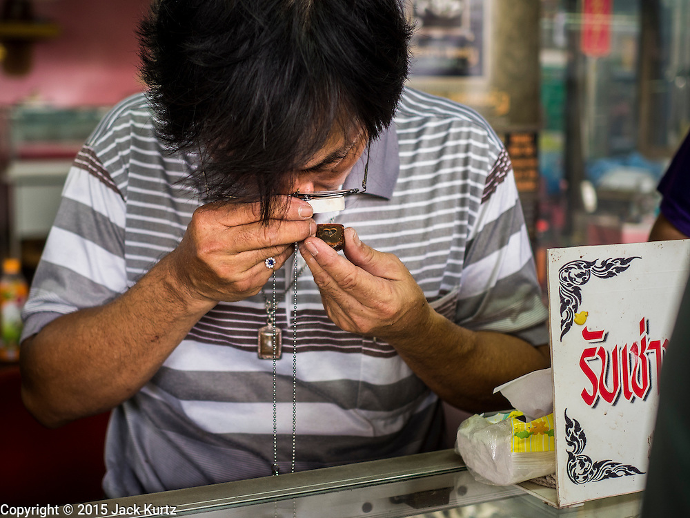 13 MAY 2015 - SAMUT SONGKRAM, SAMUT SONGKRAM, THAILAND:  An amulet vendor in the market in Samut Songkram, Thailand, examines an amulet a man was trying to sell. Amulet vendors frequently buy amulets that they then resell. In this case the vendor and the prospective seller couldn't agree on a price and the vendor did not buy the used amulet.      PHOTO BY JACK KURTZ