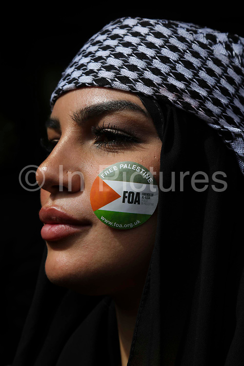 Thousands turn out in protest against the increasing use of military force by Israel and in support of Gaza on the 15th of May 2021, London, United Kingdom. A young female protester with a Free Palestine sticker on her cheek outside the Israeli embassy in Kensington High Street.  The escalating war between Israel and Hamas in Gaza is increasingly costing lives and the up to 100.000 protesters were calling for Israel to stop bombing Gaza and for a free Palestine.