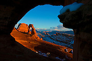 Delicate Arch, dusted by winter snow, is framed by a natural arch at sunset in Arches National Park, near Moab, Utah.