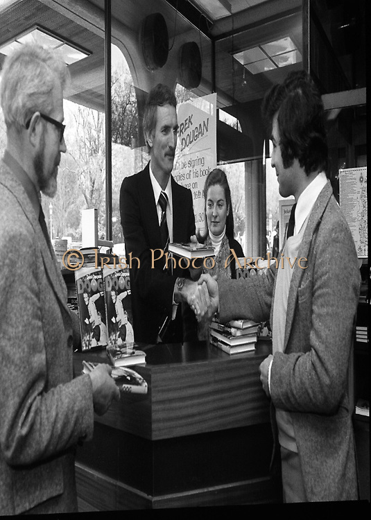 Derek Dougan gets his name on the score sheet:..1980-04-16.16th April 1980.16-04-1980.04-16-80..Photographed at Hodges Figgis, Stephen's Court, St Stephen's Green, Dublin:..Fromer Northern Irish soccer international and English League player Derek Dougan signing a copy of his book 'Doog' for customer Peter Moynihan, Sandyford, Co Dublin (right of picture)...Also in picture..Robert Twigg, manager of Hodges Figgis and cashier Norma Doyn (Tallaght, Dublin).....