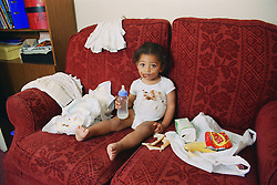 Neglected toddler sitting on sofa surrounded by dirty nappies and rubbish,