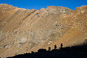 Three backpackers are silhouetted at sunrise in Sierra Nevada National Park, Andalusia, Spain.