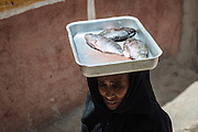 An old woman carrying fish for dinner, Seheil Island