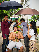 "21 JULY 2013 - BANGKOK, THAILAND:   A young man's family cuts his hair under an umbrella during a rain before he became ordained as a Buddhist monk at Wat Benchamabophit on the first day of Vassa, the three-month annual retreat observed by Theravada monks and nuns. Men frequently enter the monastery and become monks for Vassa. On the first day of Vassa (or Buddhist Lent) many Buddhists visit their temples to ""make merit."" During Vassa, monks and nuns remain inside monasteries and temple grounds, devoting their time to intensive meditation and study. Laypeople support the monastic sangha by bringing food, candles and other offerings to temples. Laypeople also often observe Vassa by giving up something, such as smoking or eating meat. For this reason, westerners sometimes call Vassa the ""Buddhist Lent.""      PHOTO BY JACK KURTZ"