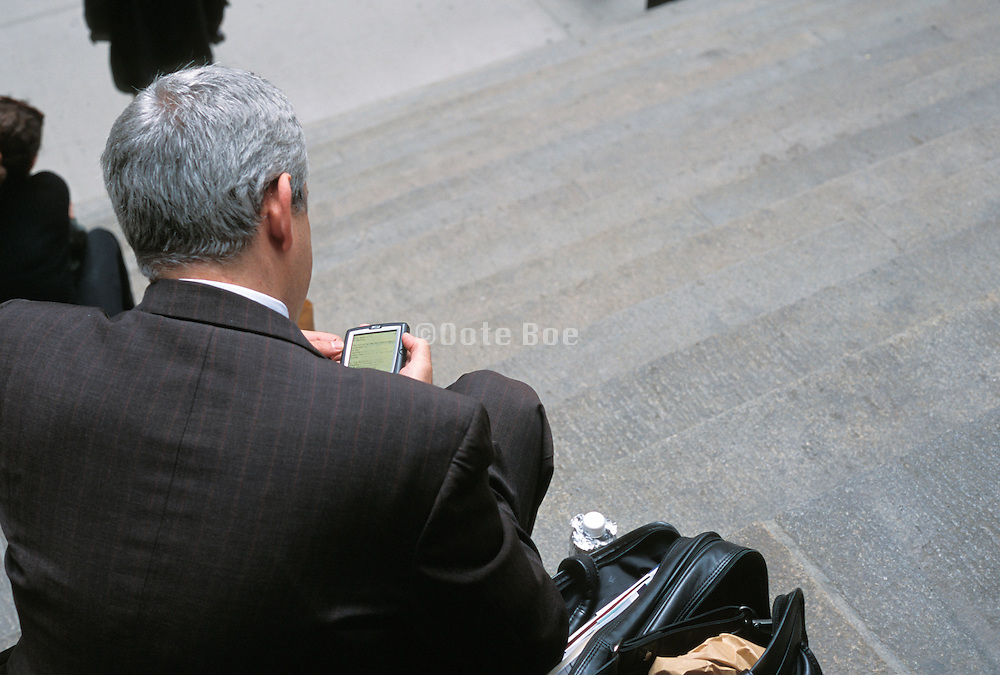 business man sitting outside going through his palm pilot