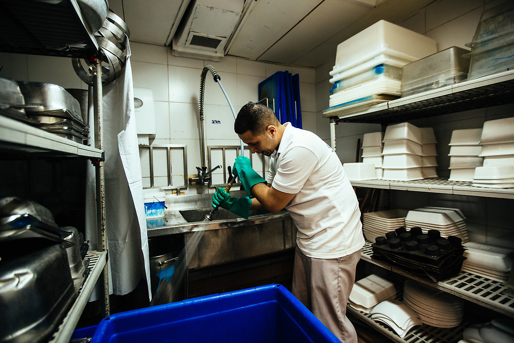 Muhammad Alsawi , 28, a Jordanian employee from Aqaba is seen cleaning the kitchen of the Isrotel Lagoona Hotel in Eilat, southern Israel, on March 14, 2018.