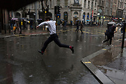 Storm Georgina swept across parts of Britain and in central London, lunchtime office workers were caught out by torrential rain and high winds, on 24th January 2018, in London, England. Pedestrians resorted to leaping across deep puddles at the junction of New Oxford Street and Kingsway at Holborn, the result of overflowing drains. Fifth in a sequence of five photos