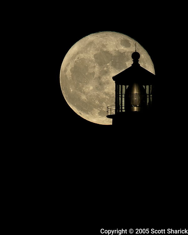A telephoto view of the full moon silhouetting the Makapuu Lighthouse on the Island of Oahu, Hawaii.