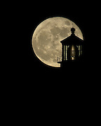 A telephoto view of the full moon silhouetting the Makapuu Lighthouse on the Island of Oahu, Hawaii.