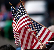 Attendees wave the American flag at the Veterans Day Parade, which honors American military veterans, in Tucson, Arizona, USA.