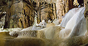 """Flowstone formations, Skocjan Caves (Skocjanske jame) Regional Park, Slovenia, Europe. Skocjan Caves feature a river raging through one of the world's largest caverns, waterfalls, speleothems (cave formations such as dripstone: stalactites and stalagmites), and twisty paths through eleven chambers over six kilometers. The underground walk over Cerkvenik Bridge 50 meters above the rushing Reka River takes your breath away in the huge Martel's Chamber (Martelova dvorana), the highest cave hall in Europe (60 meters wide and 140 meters deep, which looks bigger in the dim lighting). From a large-scale karst drainage, the Reka River has carved and dissolved dramatic subterranean passages through limestone over several million years. Archaeological finds in Tominceva Cave (Ozka spilja) indicate human occupation here from 3000 BC to 1700 BC. Modern tourism began in Skocjan Caves by 1819. Karst topography is a geologic formation of dissolving bedrock. Our word for """"karst"""" likely evolved from the Slovene noun kras and earlier proper noun Grast, referring to Slovenia's Karst Plateau. Skocjan Caves are near Divaca, in the Littoral region of the Republic of Slovenia. UNESCO has listed Skocjan Caves as a World Heritage Site."""