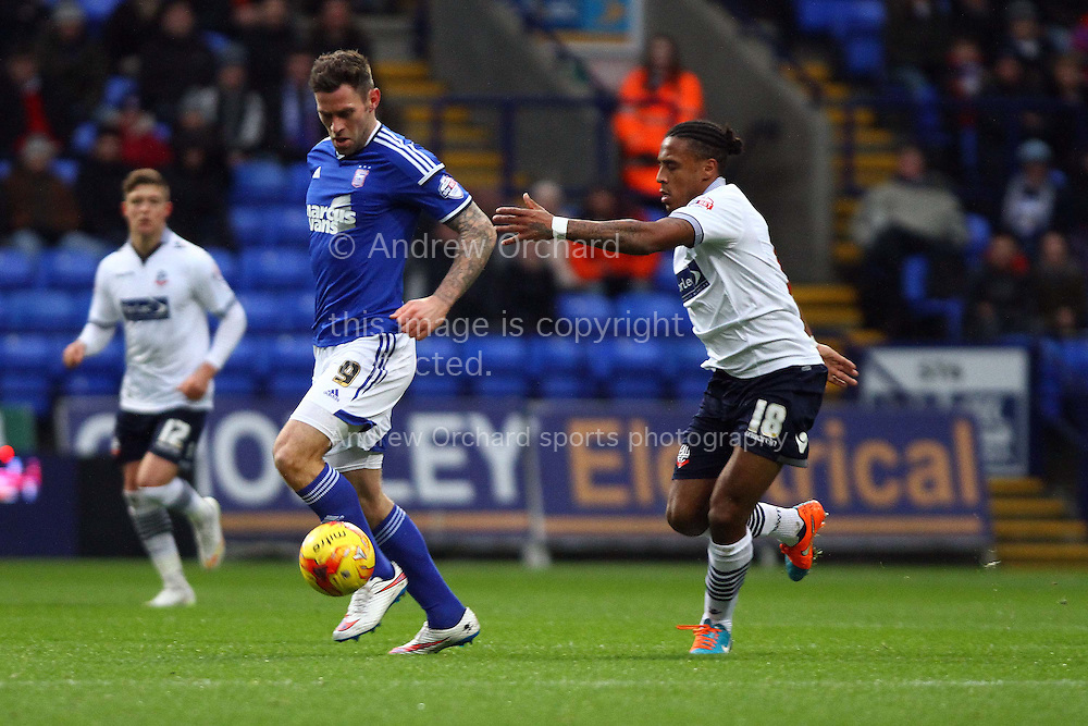 Daryl Murphy of Ipswich Town gets away from Neil Danns of Bolton Wanderers. Skybet football league championship match, Bolton Wanderers v Ipswich Town at the Macron stadium in Bolton, Lancs on Saturday 13th December 2014.<br /> pic by Chris Stading, Andrew Orchard sports photography.