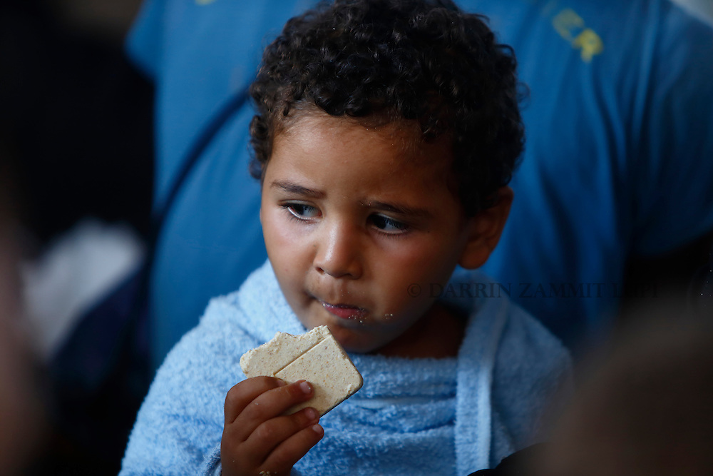 A migrant child eats emergency ration food on the Migrant Offshore Aid Station (MOAS) ship MV Phoenix after being rescued from an overloaded wooden boat 10.5 miles off the coast of Libya August 6, 2015.  An estimated 600 migrants on the boat were rescued by the international non-governmental organisations Medecins san Frontiere (MSF) and MOAS without loss of life on Thursday afternoon, according to MSF and MOAS, a day after more than 200 migrants are feared to have drowned in the latest Mediterranean boat tragedy after rescuers saved over 370 people from a capsized boat thought to be carrying 600.<br /> REUTERS/Darrin Zammit Lupi <br /> MALTA OUT. NO COMMERCIAL OR EDITORIAL SALES IN MALTA