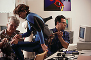 Virtual reality: fitting adjustments being made to a data suit (blue, center) by Lou Ellen Jones, Asif Emon and Bea Holster at VPL research, Redwood City, California. VPL specializes in virtual or artificial reality systems, the production of computer-generated graphical environments that users may enter. Visual contact with such artificial worlds is provided by a headset equipped with 3-D goggles. A spatial sensor on the headset (to fix the user's position in space) and numerous optical fiber sensors woven into the data suit, relay data back to the computer. The forerunner to the data suit is the data glove, which restricted the user's virtual interaction to hand gestures. Model Released (1990)