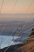Power lines and transmission towers at sunset on Stewart Mountain near Bellingham, Washington Lake Whatcom is in the distance