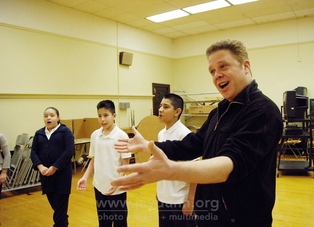 """USA, Chicago, IL, December 12, 2009.  Douglas Grew leads presentation skills practice.  Students in the """"At-Risk After School Program"""" at Maria Saucedo Scholastic Academy receive training in basic physics principles through an innovative new program called """"Circus Galactica"""" put on by Pros Arts, a non-profit organization founded in 1978 by professional artists dedicated to the Pilsen/Little Village communities. In a residency that directly integrates science and art, veteran circus performers Douglas Grew and Paul Lopez bring the importance of """"balance, focus and presentation"""" into hands-on lessons about gravity, inertia, and the dynamics of objects in motion. Photo for Hoy by Jay Dunn."""