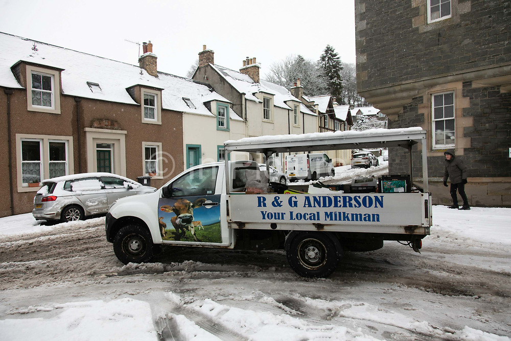Gordon Anderson on his way to deliver fresh milk and vegtables on 14th of January 2021 in Stow, Scottish Borders, United Kingdom. Gordon Anderson runs a fresh milk and vegetables delivery service with his wife and they deliver to local houses and farms in and around the village of Stow. The first real snow of the year has been falling all night and morning and the village is covered in fresh snow.